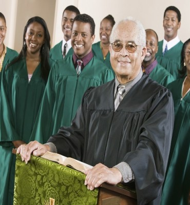 Confident Preacher Standing At Pulpit With Choir In Background