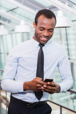 Typing business message. Cheerful young African man in shirt and tie holding mobile phone and looking at it with smile while standing indoors